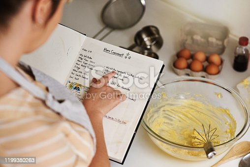 Cropped shot of an unrecognizable woman using a family recipe while baking