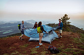 Shot of four friends setting up their tent in the mountains