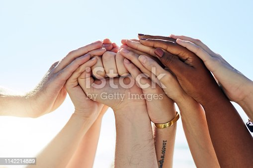 Cropped shot of a group of people joining hands in solidarity