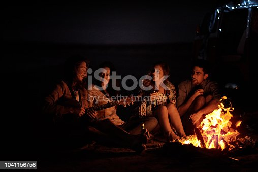Shot of a group of friends sitting around a bonfire on the beach at night