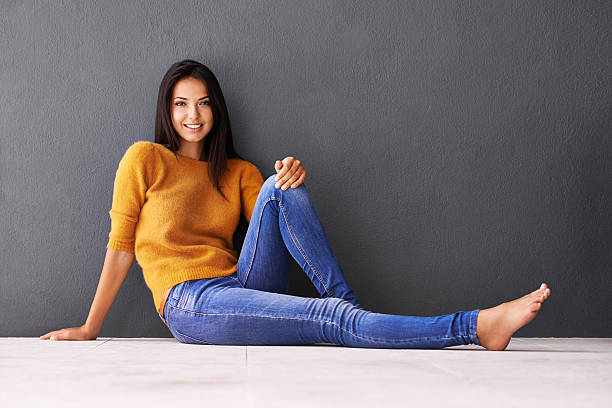 This is the life Portrait of an attractive young woman sitting on the floor against a gray wallhttp://195.154.178.81/DATA/i_collage/pi/shoots/783562.jpg skinny jeans stock pictures, royalty-free photos & images