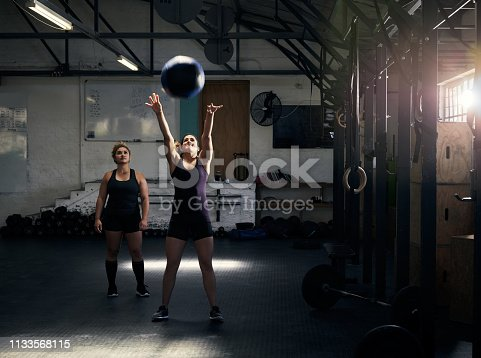 Full length shot of an attractive young woman working out with her personal trainer in the gym
