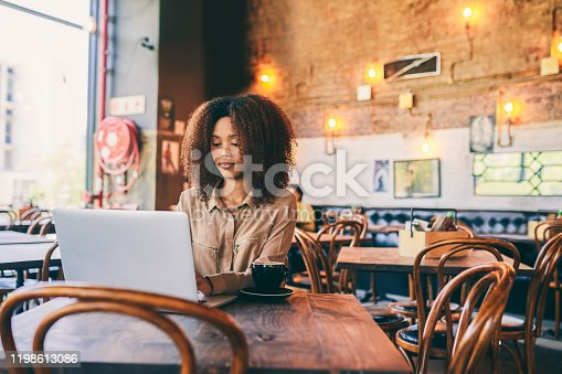 Cropped shot of a woman using her laptop while sitting in a cafe