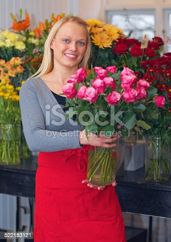 A cropped shot of a woman standing with a bouquet of flowers