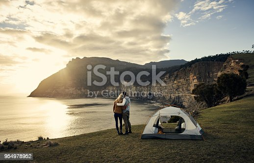 Rearview shot of an affectionate young couple standing beside their tent while camping in the mountains