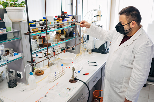 Professional male forensic scientist examines the fibers from the crime scene while holding a test tube with fibers above bunsen burner and waiting for a color change analysis in the forensic lab
