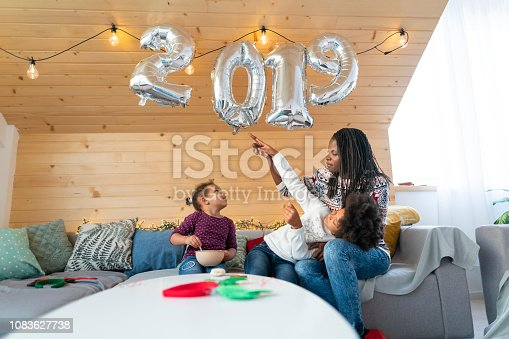 Young African - American woman enjoying new year's morning with her cute daughters.