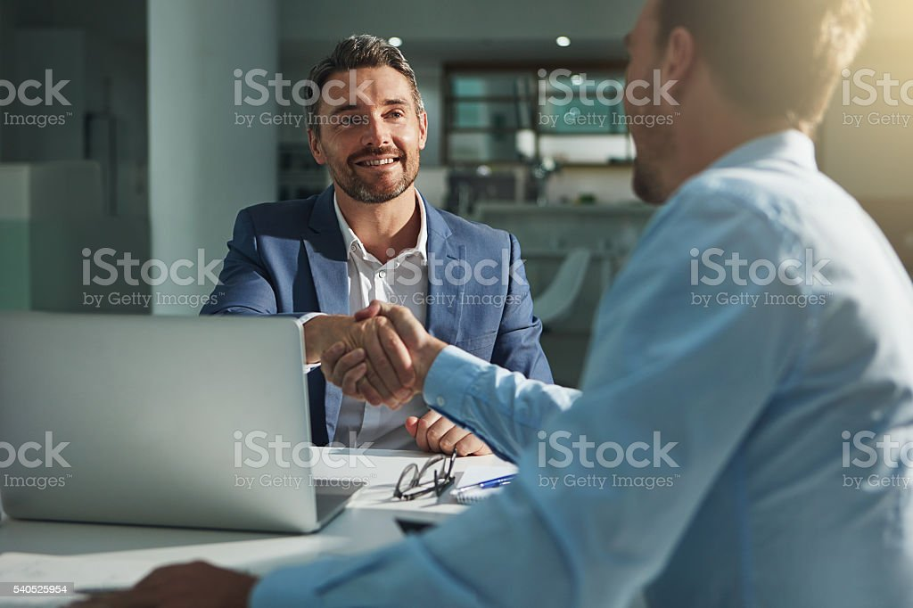 This is the start of great things Shot of two businessmen shaking hands in an office Adult Stock Photo