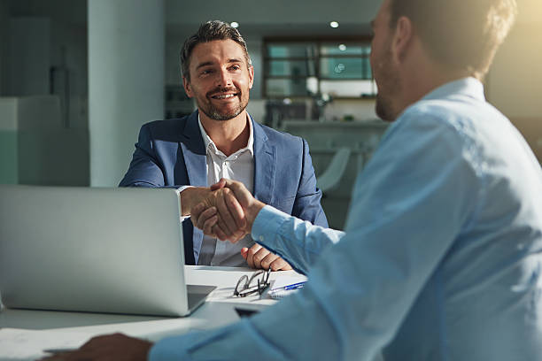 This is the start of great things Shot of two businessmen shaking hands in an office alliance stock pictures, royalty-free photos & images