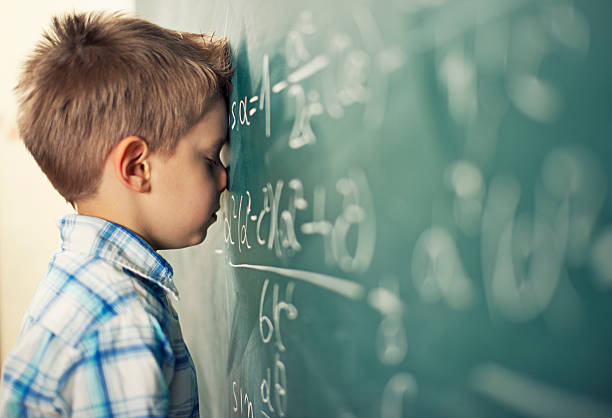 This is too hard Little boy in math class overwhelmed by the math formula. mathematical symbol stock pictures, royalty-free photos & images
