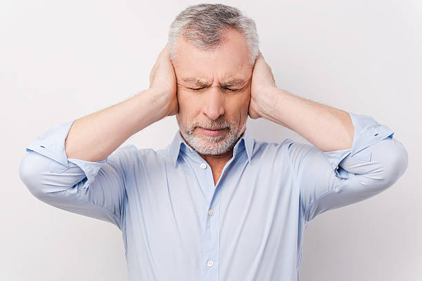 This is too loud for me! Frustrated senior man in shirt holding head in hands and keeping eyes closed while standing against grey background hands covering ears stock pictures, royalty-free photos & images