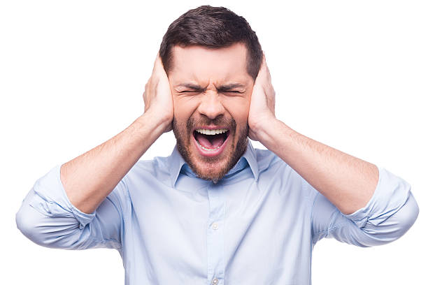 This is too loud! Frustrated young man in formalwear holding head in hands and keeping eyes closed while standing against white background hands covering ears stock pictures, royalty-free photos & images