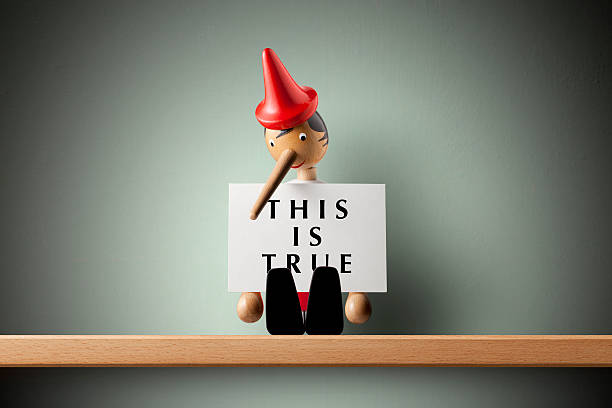 This is true. Pinocchio holding sheet of paper. Pinocchio holding sheet of paper. pinocchio stock pictures, royalty-free photos & images