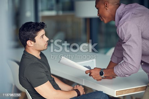 Shot of a young businessman being reprimanded by a colleague in a modern office