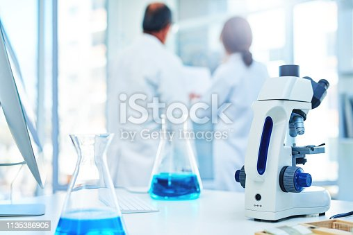 Shot of a microscope and beakers in a lab with two scientists in the background