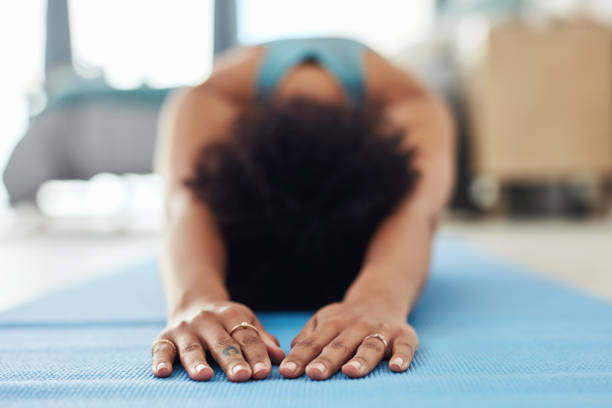 This is where peace begins Shot of a fit young woman doing yoga at home childs pose stock pictures, royalty-free photos & images