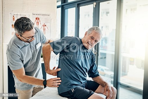 Shot of a skilled physiotherapist addressing his mature patient's back pain in the rehabilitation center