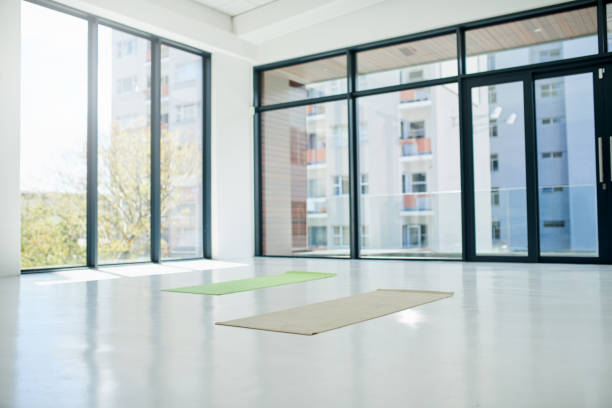 This is where the training takes place Shot of a empty yoga studio with two exercise mats in the middle of the room during the day yoga studio stock pictures, royalty-free photos & images