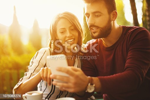 Attractive young couple having fun on a late summer afternoon. Man showing his girlfriend a new travel destination for their next vacation.