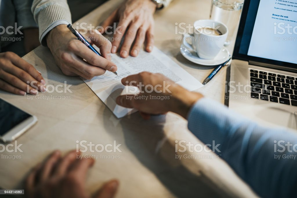 This is where you need to sign! Unrecognizable man signing a contract while financial advisor is aiming at the place he need to sign. Adult Stock Photo