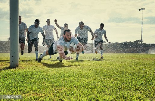 Full length shot of a handsome young rugby player scoring a try while training on a rainy day