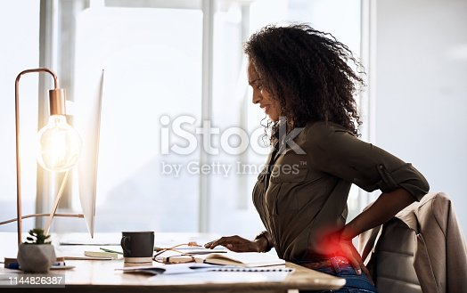 Shot of a businesswoman suffering from back pain while sitting at her desk