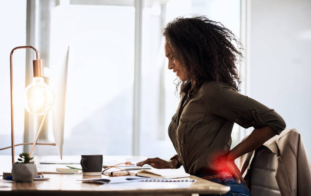 This is why stretching is important Shot of a businesswoman suffering from back pain while sitting at her desk back pain stock pictures, royalty-free photos & images