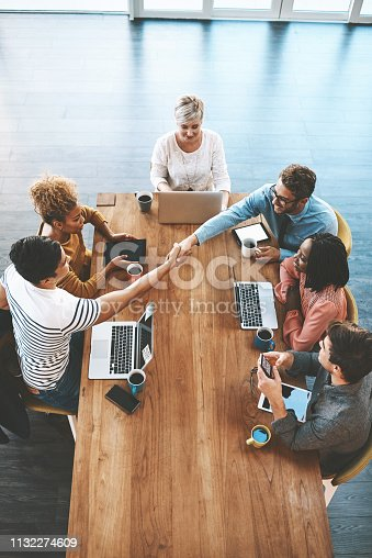 Shot of a colleagues shaking hands during a meeting in a modern office