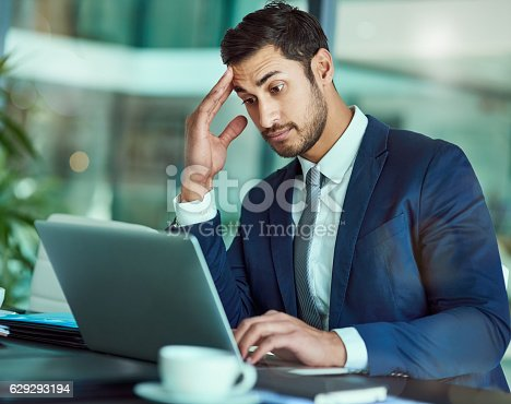 Shot of an stressed executive working on a laptop in an office
