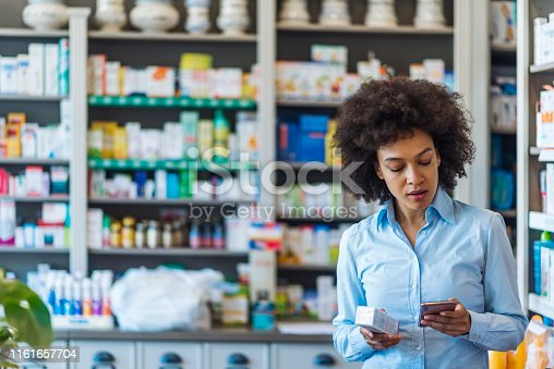 Photo of mixed race woman using mobile phone searching information and reading medicine label and prescription medications. Health care and people concept. Female holding medications while searching for instruction on the internet using her smartphone reading about the product, technology online research.