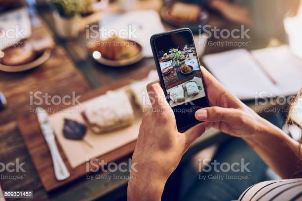 Cropped shot of a woman taking a picture on her phone of her food
