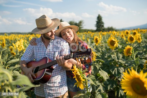 Young man playing the guitar, standing with his girlfriend in the field of sunflowers in bloom.