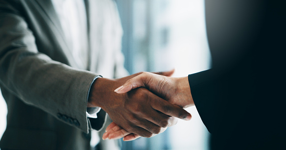 Closeup shot of two unrecognisable businesspeople shaking hands in an office