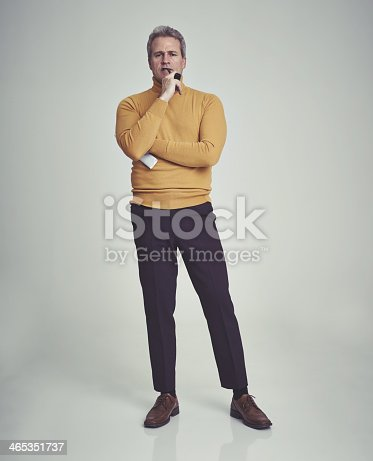 Studio shot of a mature man striking a thoughtful pose while wearing retro 70s style clothing
