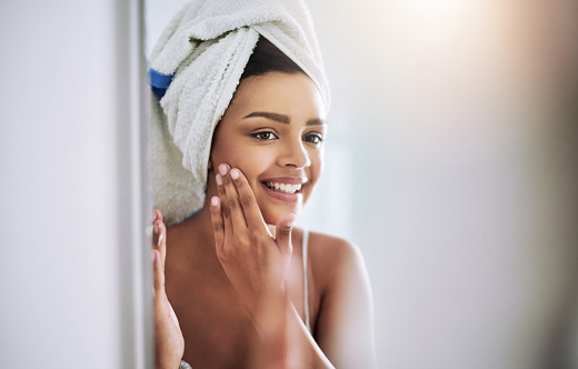 Shot of an attractive young woman applying moisturizer to her face in the bathroom
