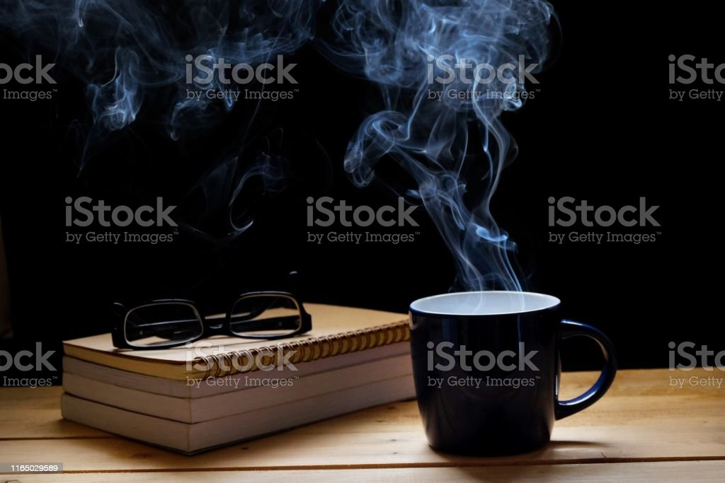 This morning a cup of hot coffee smoke and a book on wood table