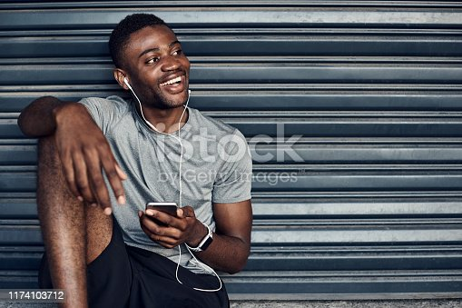 Shot of a sporty young man wearing earphones while using a cellphone against a grey background