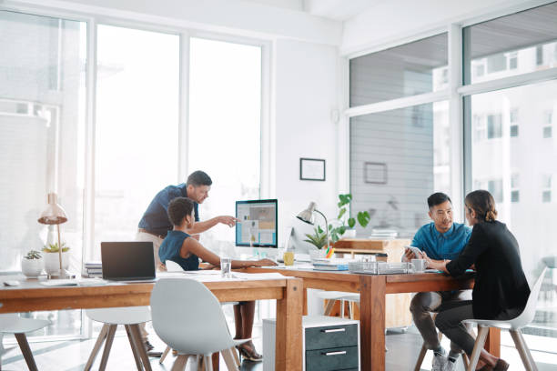 This office runs on teamwork Shot of a team of businesspeople working together in a modern office coworking stock pictures, royalty-free photos & images