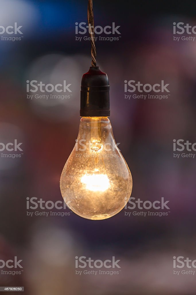 This old light bulb is hanging from a wire stock photo