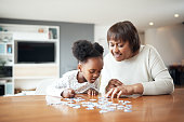 Shot of a little girl building a puzzle with her grandmother at home