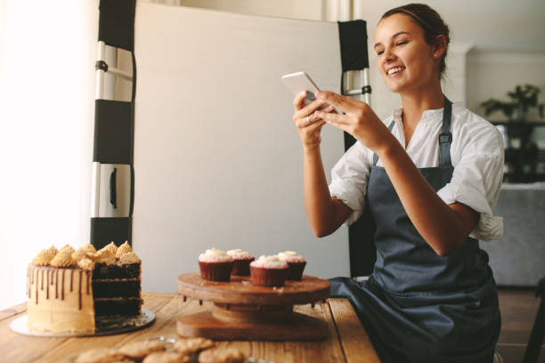 This one for my food blog profile Happy woman chef taking a picture of pastries on a wooden board with smart phone while standing at the kitchen. Female baker taking pictures of the dessert for her food blog. jacoblund stock pictures, royalty-free photos & images