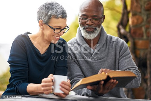 Cropped shot of an affectionate senior couple reading their bible while sitting outside