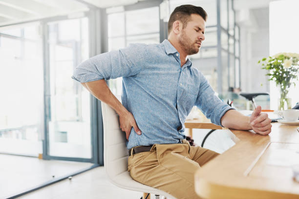 This pain is becoming far too unbearable Cropped shot of a young businessman experiencing back pain while working at his desk back pain stock pictures, royalty-free photos & images