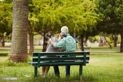 Rearview shot of an affectionate senior couple sitting on a bench in the park