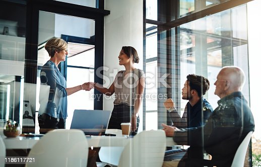 Shot of two businesswomen shaking hands together during a boardroom meeting at work