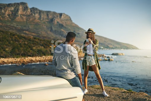 Shot of a young couple making a stop at the beach while out on a roadtrip