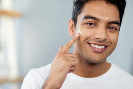 Cropped shot of a handsome young man applying moisturizer to his face