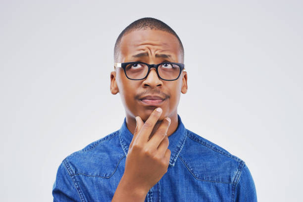 This puts me in a awkward position Studio shot of a young man looking thoughtful against a gray background uncertainty stock pictures, royalty-free photos & images
