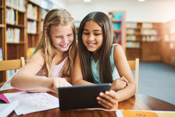 This really helps with homework Shot of two cheerful young school girls working together in a classroom with a digital tablet  at school during the day cute middle school girls stock pictures, royalty-free photos & images