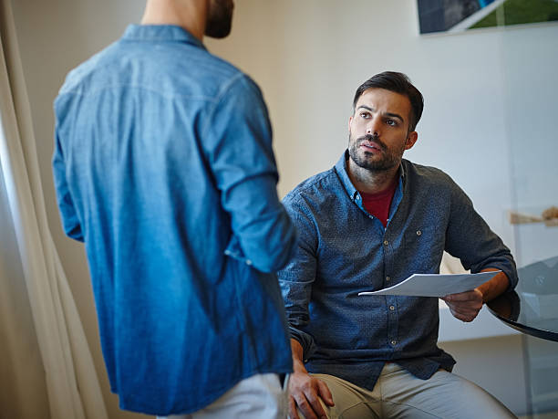 This report needs finishing asap! Shot of two young businessmen talking together at a desk in an office ASAP stock pictures, royalty-free photos & images